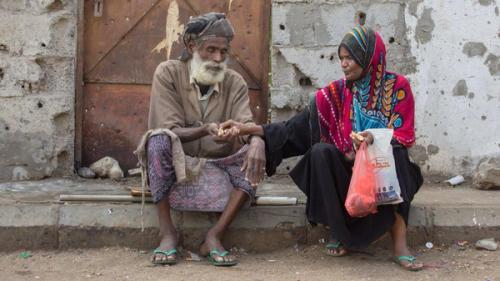 """صورة معبرة.. مسنان يمنيان يتقاسمان """"لقمة العيش"""""""