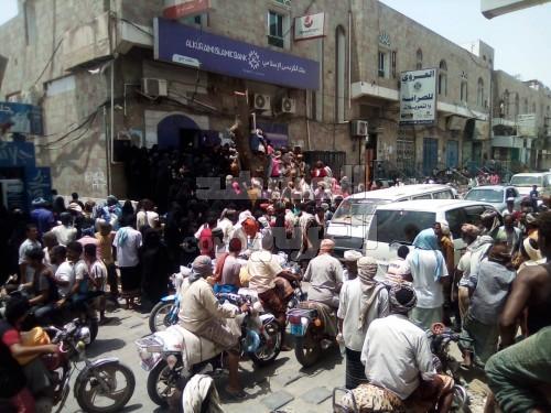 إصابات وحالات إغماء أمام أبواب مصرف الكريمي بلحج (صور)